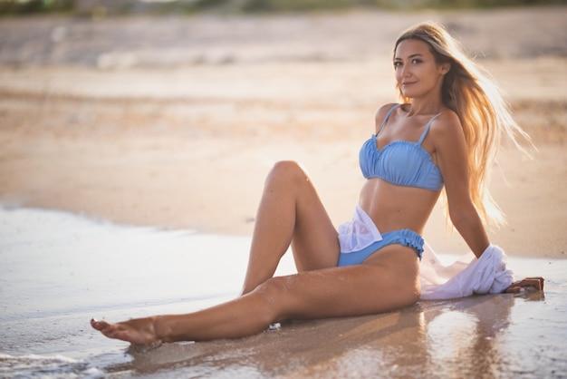 青みがかった水着と真っ白なシャツを着た美しい日焼けしたほっそりした女の子は、海の端の近くに座って、暖かい晴れた夏の日に地平線をのぞき込みます
