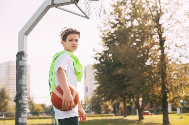 美しいティーンエイジャーは彼の手でバスケットボールを持って、カメラを見ます。