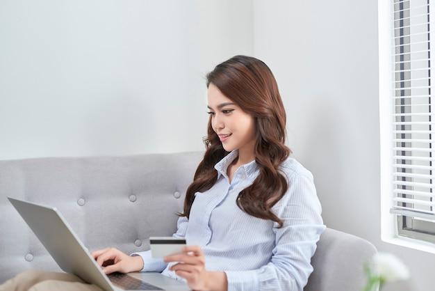 Красивая, используя ноутбук и свою банковскую карту, делая покупки из дома без живого дивана