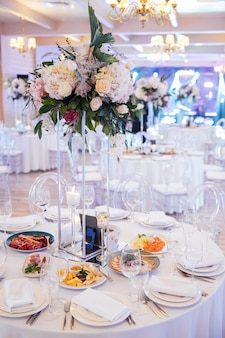 Красивая ваза с цветами на столе в роскошном ресторане. свадебный декор