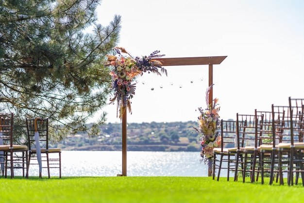 야외 결혼식을위한 아름다운 장소. 웨딩 아치와 강이 내려다 보이는 녹색 잔디밭에 손님 의자 행