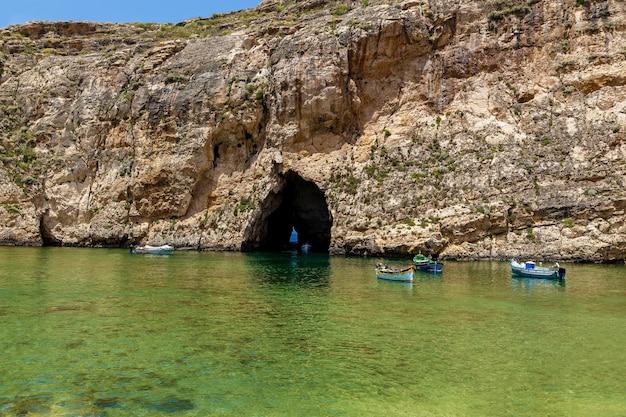 晴れた日の海の洞窟の前に白い観光船が見える美しい景色。洞窟の入り口近くにはたくさんのボートがあります。