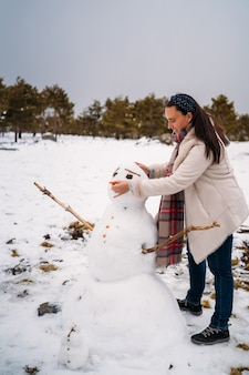 Красивая теплая женщина играла со снеговиком - концепция отпуска - вертикальное изображение