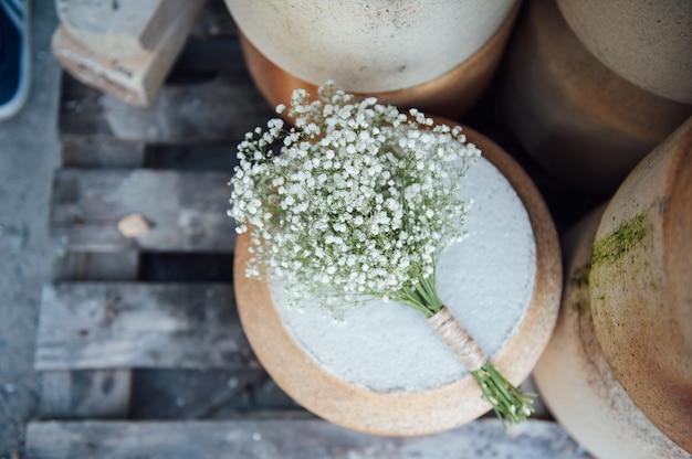 カスミソウの美しいウェディングブーケは、粘土の水差しにあります。