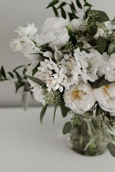 아름다운 웨딩 부케가 꽃병에 담겨 있습니다.