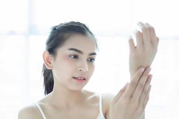 그녀의 건조한 안색을 돌보는 스킨 케어 제품, 로션 또는 로션을 사용하여 아름다운 여자 아시아. 여성의 손에 보습 크림.