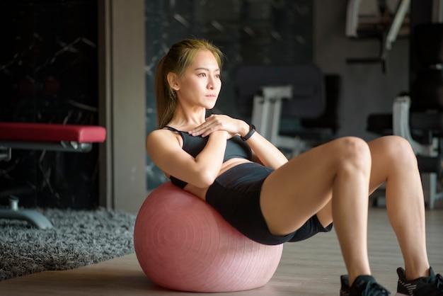 Красивая женщина в тренажерном зале, тренирующаяся с мячом для наращивания мышц, концепция здорового образа жизни, спорта, тренировок, благополучия и спорта