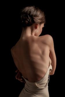美しい女性、暗い背景の背面図