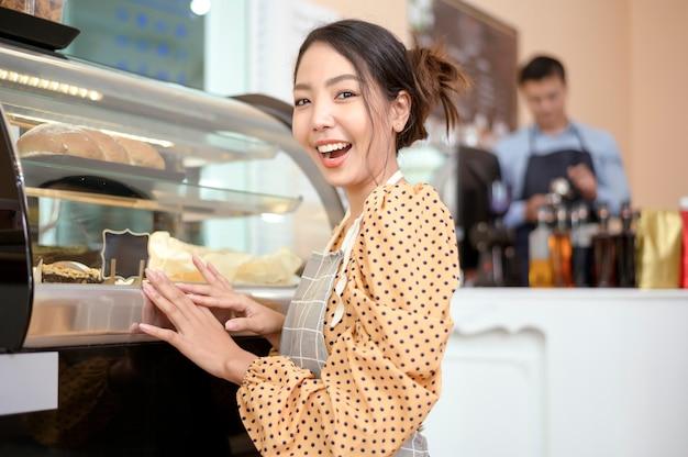 아름다운 여성 빵집이나 커피숍 주인이 가게에서 웃고 있다