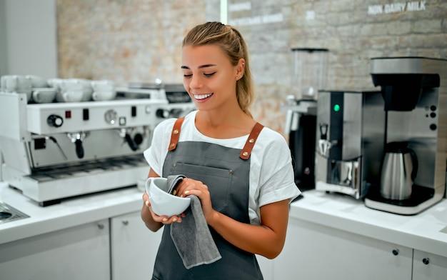 Красивая женщина-бариста в фартуке моет тряпкой чашку за барной стойкой в кофейне.