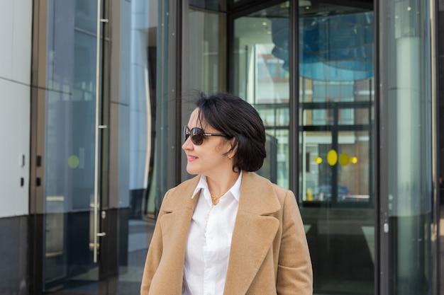 ビジネスセンターのドアから美しい女性が出てきて微笑む。