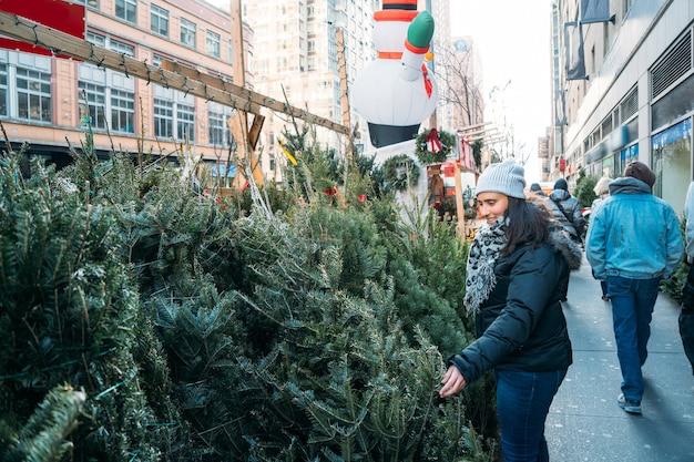 뉴욕의 크리스마스 거리에서 작은 소나무를 관찰하는 코트를 입은 아름다운 여성