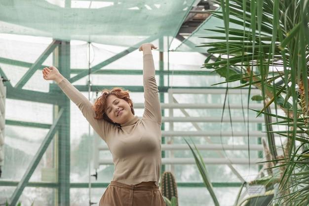 녹색 식물 가운데 서 즐기는 아름다운 여인