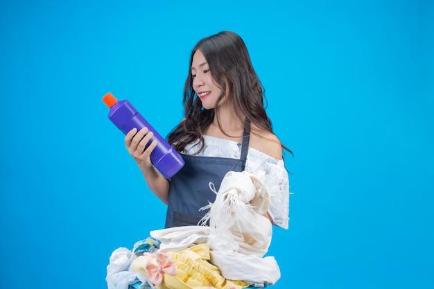 Красивая женщина, держащая ткань и жидкое моющее средство, подготовленные для стирки на синем