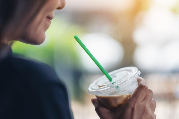 飲むためにアイスコーヒーのプラスチックガラスを保持している美しい女性