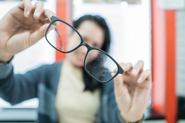 眼鏡のディスプレイウィンドウに対して眼科クリニックで眼鏡のサンプルを保持している美しい女性