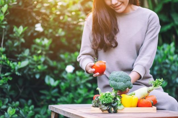 Красивая женщина, держащая и собирающая свежую овощную смесь с деревянного подноса на столе