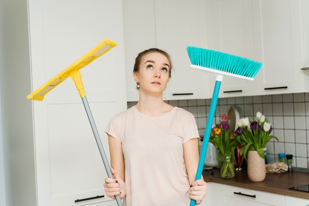 美しい女性は、掃除とモップ拭きのためにモップとブラシを手に持っており、疲労のため息をつきます。主婦が台所に立ち顔から汗を拭く