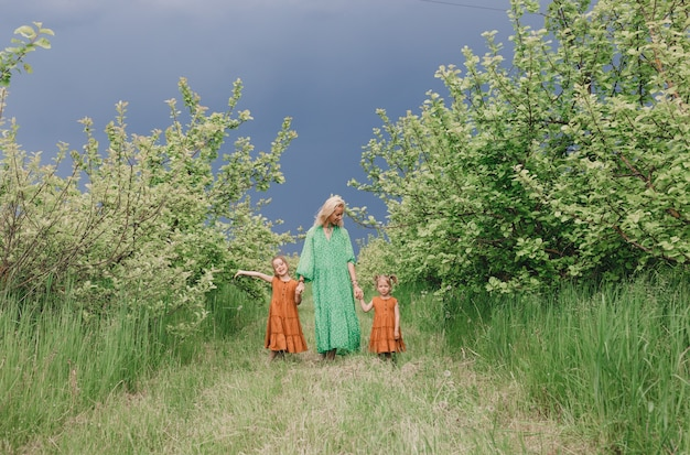 緑のドレスを着た美しい女性が、雨の前に2人の子供と一緒に庭を歩いています。歩くお母さんと娘