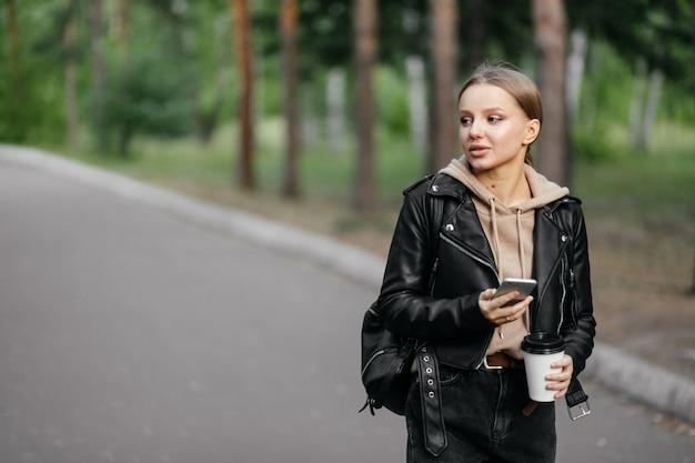 革のジャケットを着た美しい女性が公園を散歩し、電話と彼女の手でコーヒーを飲みながら側を見ながらかなり笑顔