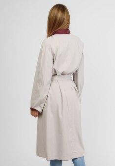 흰색 배경에 가벼운 가을 코트를 입은 아름다운 여자. 가게 사진.