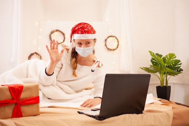 마스크와 크리스마스 모자를 쓴 아름다운 여인이 화상 통화로 온라인에서 친구를 축하합니다.