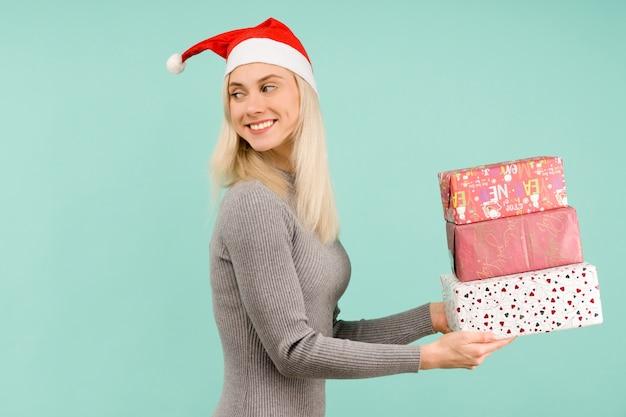 新年の帽子と灰色のドレスを着た美しい女性は、クリスマスや新年のお祝いの贈り物を手に持っています