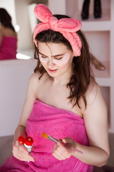 Красивая женщина в розовом полотенце и с косметической повязкой на голове собирается выжать косметическую маску.