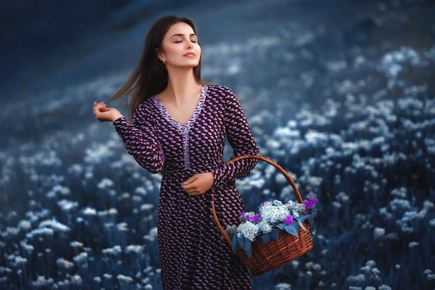 麦わらバスケットを手に、咲く花の畑で夏のドレスを着た美しい女性