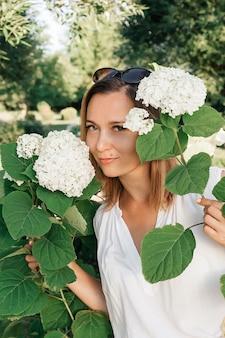 Красивая женщина в летнем парке. портрет женщины с цветами.