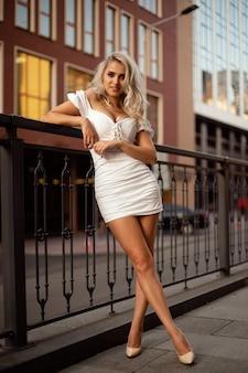 К перилам прислонилась красивая женщина в белом платье.