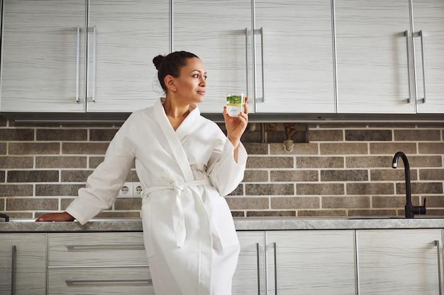 白いワッフルのローブを着た美しい女性が台所のカウンターに寄りかかって目をそらし、健康的な朝の習慣としてレモン水を飲んでいます。