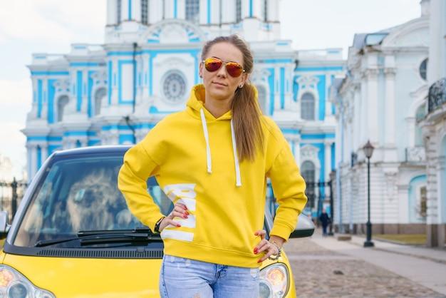 春の日に街の車の前でポーズをとる黄色いパーカーの美しい女性