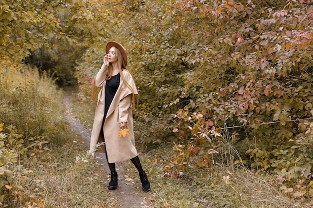 自然の中で秋の服を着た美しい女性。秋のブログ