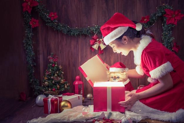 산타 클로스 의상과 귀여운 강아지 강아지 포메라니안을 입은 아름다운 여인은 메리 크리스마스와 새해 복 많이 받으세요에 선물 상자를 열어 기뻐했습니다. 프리미엄 사진