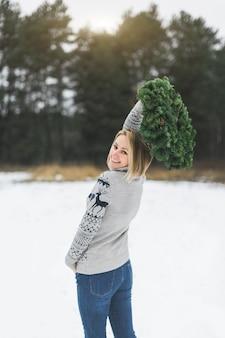 Красивая женщина в свитере и джинсах держит рождественский венок на открытом воздухе