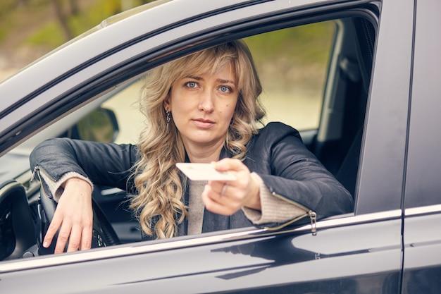 자동차 창문에 아름다운 여성이 운전 면허증을 보여줍니다