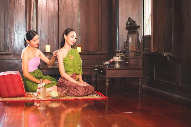 伝統的なタイのドレスを着た美しい女性が、木造住宅で上司の女性のスキンケアをしています。過去のアユタヤ王朝の人々の生活の概念