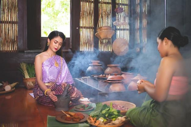 伝統的なタイのドレスを着た美しい女性が、材料の準備の隣に座っている使用人と一緒にキッチンで唐辛子ペーストを叩くために乳鉢を使用しています。タイの人々の料理の概念で