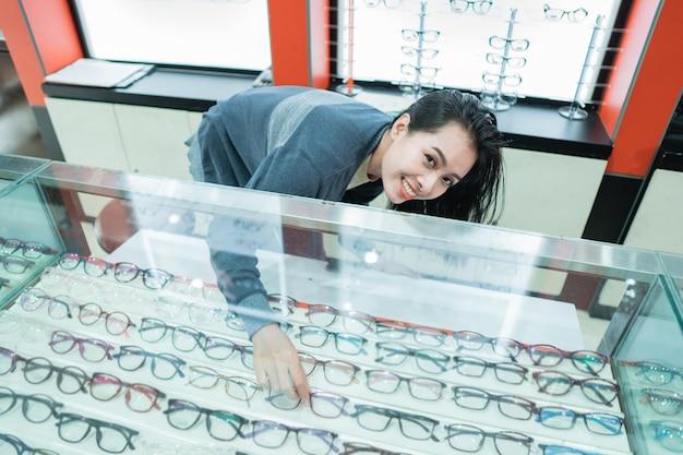 美しい女性は、眼鏡ショーケースの背景に対して眼科クリニックのショーケースにある眼鏡フレームを選択しています