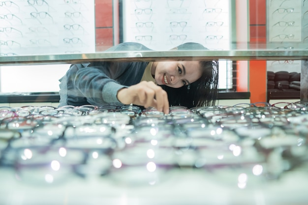 美しい女性が眼鏡ショーケースに対して眼科クリニックのショーケースにある眼鏡フレームを選んでいます