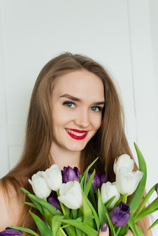 美しい女性が大きな花束を持っています。チューリップの花束を持つ若い女性