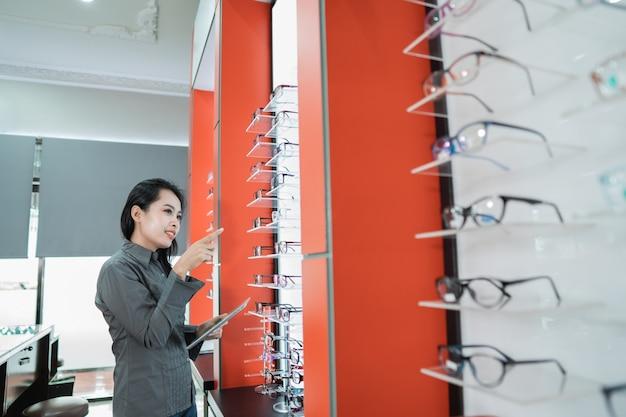 美しい女性が眼科クリニックで視力検査を受けた後、入手可能な眼鏡製品のカタログを持っています
