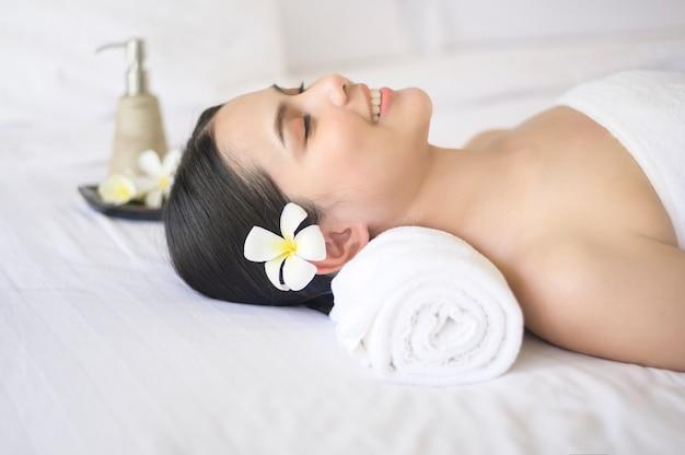 Красивая женщина расслабляется и делает массаж на спа-курорте, концепция массажа и косметических процедур.