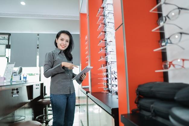 美しい女性が、眼科クリニックで視力検査を受けた後、入手可能な眼鏡製品のカタログを見せています。