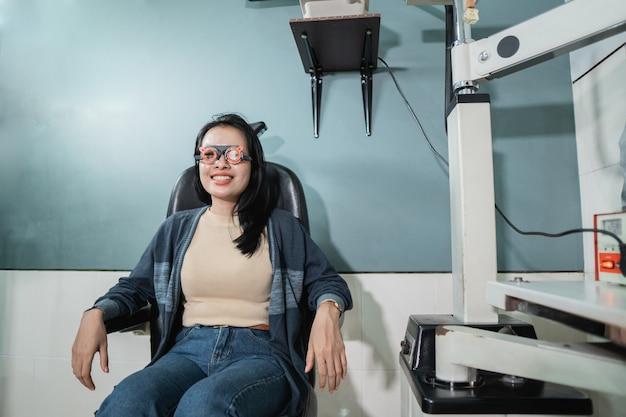 美しい女性が椅子に座って、目のチェックのために眼科クリニックで実験的な眼鏡フレームを着用しています