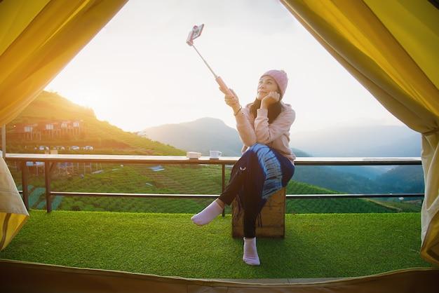 美しい女性が朝、テントで携帯電話を使って自分撮りをしています。