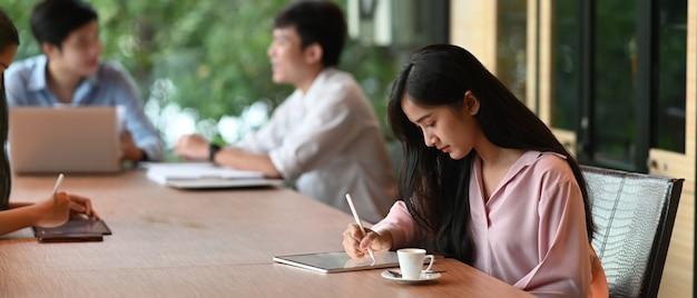 美しい女性が会議室に座っているときにコンピューターのタブレットとスタイラスペンを使用しています。