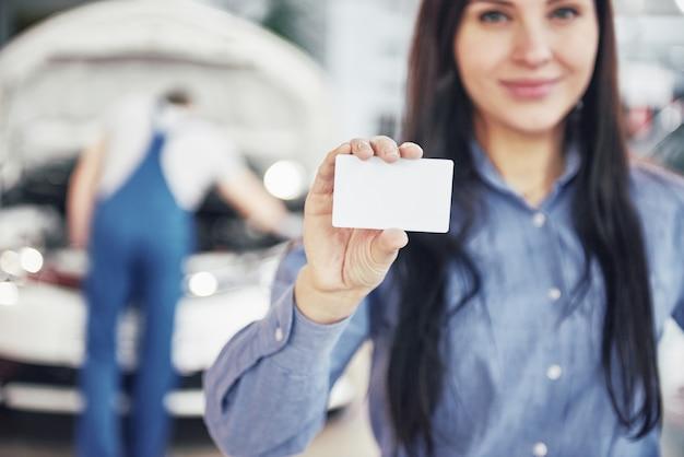Красивая женщина держит визитную карточку автосервиса. механик осматривает машину под капотом на заднем плане