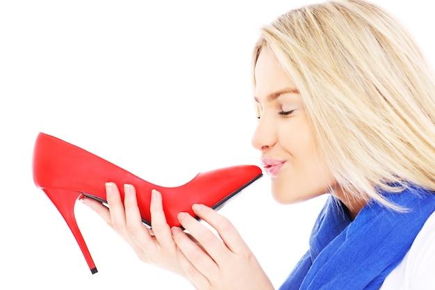 흰색 배경 위에 그녀의 빨간 발 뒤꿈치를 키스하는 아름다운 여자